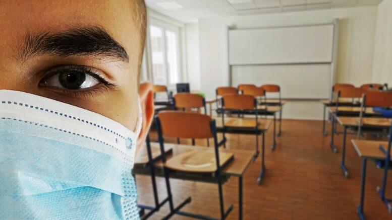 Schüler mit Maske im leeren Klassenzimmer